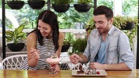 Pares felizes do  de Ð que comem uma sobremesa no café Menina que alimenta seu noivo vídeos de arquivo