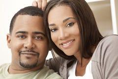 Pares felizes do americano africano que sentam-se em casa Imagens de Stock