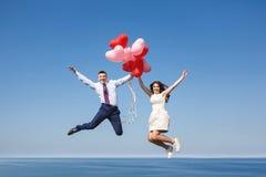 Pares felizes do casamento com balões vermelhos Fotos de Stock Royalty Free