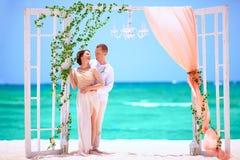 Pares felizes do casamento na praia tropical decorada Fotos de Stock Royalty Free