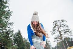 Pares felizes do curso do inverno Homem que dá o passeio do reboque da mulher em férias do inverno na floresta nevado fotos de stock