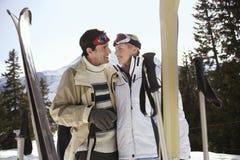 Pares felizes do esqui na roupa morna com esquis Fotografia de Stock