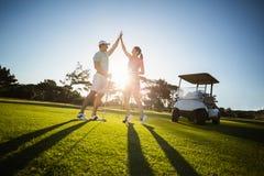 Pares felizes do jogador de golfe que dão a elevação cinco foto de stock