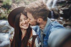 Pares felizes do moderno que tomam o selfie na cachoeira em estiletes da floresta Imagem de Stock Royalty Free