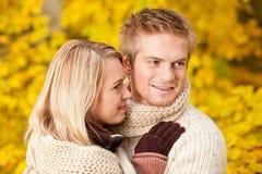 Pares felizes do outono que abraçam junto o cenário do parque imagens de stock