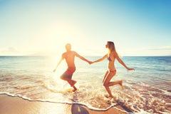 Pares felizes do por do sol na praia fotografia de stock royalty free