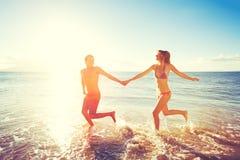 Pares felizes do por do sol na praia imagens de stock royalty free