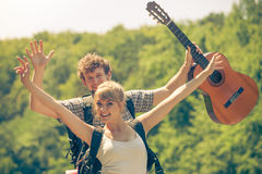 Pares felizes do turista com a guitarra exterior Fotografia de Stock Royalty Free
