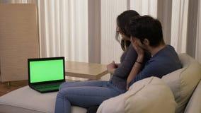 Pares felizes em casa que olham um filme da comédia em um portátil com a tela verde que ri e que tem uma boa estadia video estoque