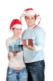 Pares felizes em chapéus de Santa Imagens de Stock Royalty Free