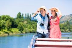 Pares felizes em chapéus vestindo do sol do cruzeiro do rio no verão imagem de stock