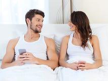 Pares felizes em uma cama com telefones celulares Imagens de Stock