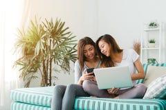 Pares felizes lésbicas asiáticos novos bonitos das mulheres LGBT que sentam-se no sofá que compra em linha usando o portátil um c Foto de Stock