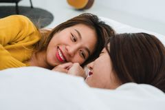 Pares felizes lésbicas das mulheres asiáticas novas bonitas que abraçam e que sorriem ao encontrar-se junto na cama sob a cobertu imagem de stock