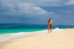 Pares felizes loving novos na praia tropical foto de stock royalty free