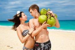 Pares felizes loving novos na praia tropical, com cocos Imagem de Stock