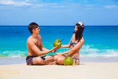 Pares felizes loving novos na praia tropical, com cocos Fotografia de Stock Royalty Free