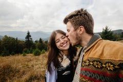 Pares felizes macios de viagem bonitos à moda nas montanhas Imagens de Stock