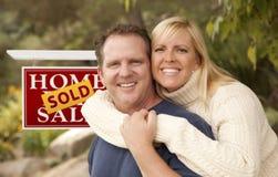 Pares felizes na frente do sinal vendido dos bens imobiliários Imagens de Stock Royalty Free