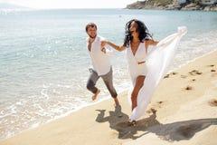 Pares felizes na lua de mel em Grécia, no sorriso e na corrida na praia, horas de verão, dia ensolarado fotografia de stock
