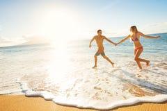 Pares felizes na praia tropical no por do sol fotos de stock
