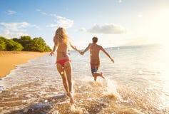 Pares felizes na praia tropical no por do sol imagens de stock royalty free