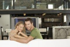 Pares felizes na sala de visitas com a televisão do plasma no fundo Fotografia de Stock