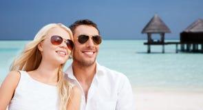 Pares felizes nas máscaras sobre a praia com bungalow foto de stock royalty free