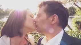 Pares felizes no amor que beija na frente do lago no movimento lento do por do sol filme