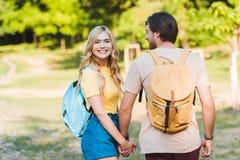 pares felizes no amor que guarda as mãos ao andar no verão imagens de stock