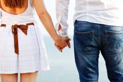 Pares felizes no amor que guarda as mãos perto do mar Fotografia de Stock Royalty Free