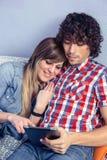 Pares felizes no amor que olha a tabuleta eletrônica sobre fotos de stock royalty free
