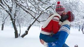 Pares felizes no amor que tem o divertimento, abraçando e beijando no inverno video estoque