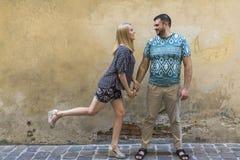 Pares felizes no amor que tem o divertimento contra a parede da casa velha Imagem de Stock Royalty Free