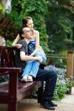 Pares felizes no banco de parque Foto de Stock Royalty Free
