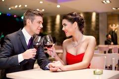 Pares felizes no brinde da tabela do restaurante foto de stock royalty free