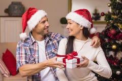 Pares felizes no chapéu de Santa que guarda o presente Fotografia de Stock