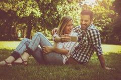 Pares felizes no parque Pares felizes que tomam a autoimagem com Fotografia de Stock Royalty Free