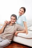 Pares felizes no sofá na vida fotografia de stock royalty free