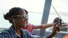 Pares felizes nos óculos de sol que tomam o selfie usando o telefone que sorri ao flutuar em férias Movimento lento 1920x1080 vídeos de arquivo