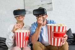 pares felizes nos auriculares da realidade virtual que comem a pipoca junto fotos de stock