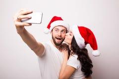 Pares felizes nos chapéus de Santa que tomam a imagem do selfie das mãos Foto de Stock