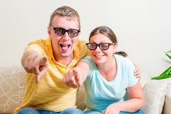 Pares felizes nos vidros 3D que olham a televisão Fotos de Stock