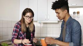 Pares felizes novos bonitos que sentam-se na cozinha, alimentando-se croissant, comendo o café da manhã maravilhoso junto dentro vídeos de arquivo