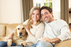 Pares felizes novos com o cão que senta-se no sofá Fotos de Stock Royalty Free