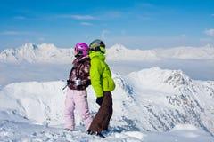 Pares felizes novos em montanhas do inverno Imagens de Stock