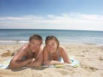 Pares felizes novos na praia Imagem de Stock
