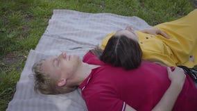 Pares felizes novos no amor que faz o piquenique que encontra-se junto no jardim ou no parque de florescência bonito que relaxam  filme