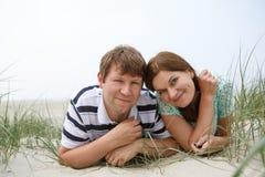Pares felizes novos no amor que tem o divertimento em dunas de areia da praia Fotos de Stock Royalty Free