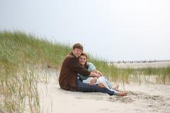 Pares felizes novos no amor que tem o divertimento em dunas de areia da praia Fotografia de Stock Royalty Free